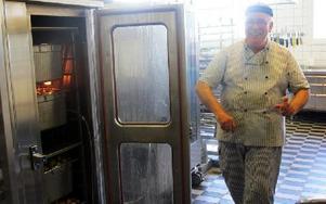 Panos Baisakos öppnar dörren till värmeskåpet där potatisen står. FOTO: LINNEA JOHANSSON