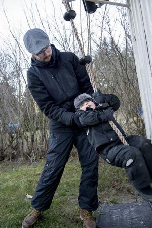 Vid vedboden hänger ett klätterrep men det är svårt att komma upp utan pappas hjälp.