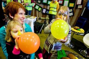 """Systrarna Edfeldt, Elina, 7 år, och Ella, 5 år, hade gått tipspromenaden tidigare under dagen, men nu var det tid för ballonger och ansiktsmålningar. Elina berättar att hon brukar säga åt sin mamma Sara att inte spola så mycket kranvatten. """"Men hon lyssnar aldrig"""", lägger hon till. Mamma Sara skrattar.   Foto: Ulrika Andersson"""