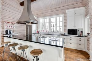 Köket är topputrustat och har ekgolv och vitlaserade timmerväggar.