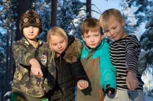 Linus Andersson, Hanna Rönnberg, Anton Strand och Alvin Asplind pekar på älgspåren i snön alldeles i närheten av skolan.