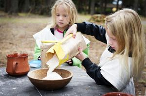 Anna Arnmark och Julia Gyllenflykt mäter upp kornmjöl till kams. Sedan ska det bara till salt och vatten.