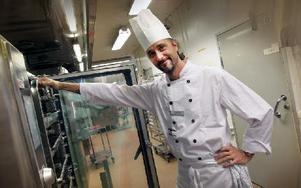 Kocken Mikael Gruddpers, har jobbat här i ett år. Han kommer tidigare från restaurangbranschen och inom skolkök i Vansbro. Han ställer in formar med lax- och fiskfärsrutor i ugnen. Sedan har han en mall med rutor som han trycker på maten och det blir färdiga portioner. Foto: Staffan Björklund