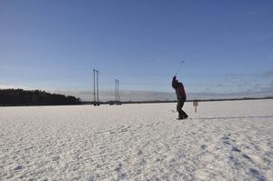 Leif Jansson slår en golfsving ute på isen i Marma.