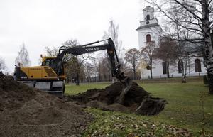 Här återställer kommunen marken efter vattenläckan vid Forsa kyrka.