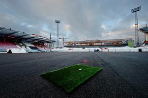 Kallt väder har satt käppar i hjulet för det nya konstgräset på Behrn arena. Nu har Örebroporten hyrt in ett tält för att få upp värmen där gräset ska läggas.