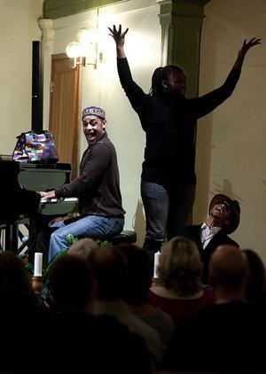 Joshua Nelson sitter vid pianot och sjunger med sångaren Jeremiah Williams manar på kören under gårdagens övningar i Elimkyrkan.