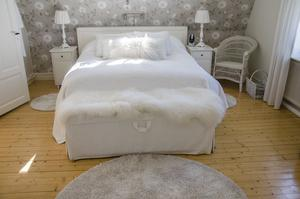 Sovrummet går i ljusa toner och sängen är mysigt bäddad med mycket textilier.
