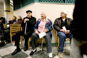 """Lennart Backström, Inga-Britt Grundstedt och Alf Löfman har väntat i en halvtimme och har inte ens börjat köa än eftersom de inte orkar stå. """"Bered dig på tålamod"""", säger Inga-Britt Grundstedt."""