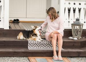 Maria Kättström och hunden Ronja myser på trappen till huset i Myrby.
