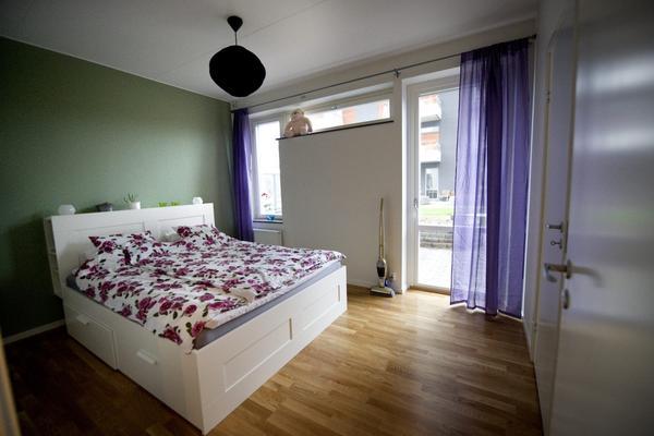 På en av väggarna i sovrummet fick de välja färg, och det blev en mild grön nyans som passar fint med lila och blommigt. Det är inte så mycket förvaringsutrymmen i lägenheten så en säng med lådor under är ett bra komplement. Detta är Brimnes från Ikea.