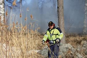 Erkki Nivala är byalaget starke man i sådana här tillfällen. I bakgunden ligger röken tjock efter fullmatning av vass och sly i elden. Bild: Morgongåva Bild & Foto.