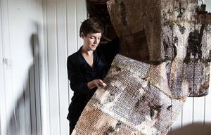 Emma Dahlqvist håller upp ett av sina arbeten. Här har hon skurit ut mönster i nävern så att hela biten rullar ihop sig. En bit på 40 gånger 40 centimeter tar ungefär 40 minuter för laserskäraren att skära ut.