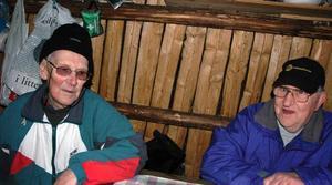 Värdar. Göte Löwes och Stig Andersson var värdar första dagen vid Tallmorkojan. Här värmer de sig inne i kolarkojan.