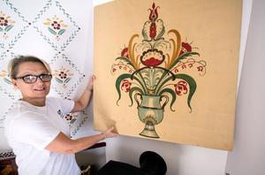 Kristina Leijonhufvud visar upp tavlan med kurbitsmålningen som härstammar från det gamla Elsas. Till vänster syns delar av handmålningarna på väggen.