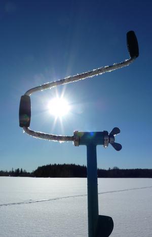Isfiske en solig vinterdag på sjön Bågen i Karbenning
