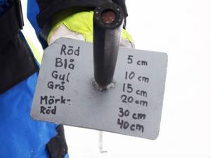 Mätstaven är tejpad med olika färger för att lätt kunna läsa av isens tjocklek.