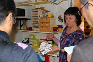 Birgitta visar besökarna ett av förskolans pedagogiska medel.