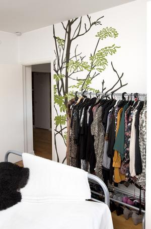 Dekor och förvaring. Fondtapeten och en garderobshäst blir ett dekorativt blickfång vid sängens fotände.
