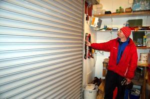 Vaktmästare Per-Olov Bergman visar hur tjuvarna hade tagit sig in i garaget för ismaskinen för att sedan öppna skjutdörren som går in i ishallen.