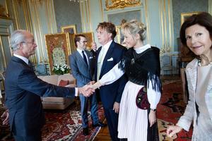KUNGLIG HÄLSNING. Tony Warrens sambo Lena Jonsson hälsar på kungen och drottning Silvia. Kungen var särskilt intresserad av riksäpplet som Tony målat.