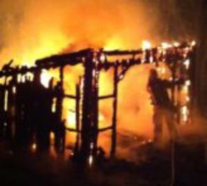 Räddningstjänsten släcker brand i övertänt vindskydd.