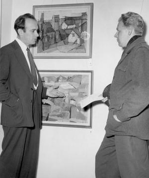 Pedagogen i verksamhet framför egna målningar, okänd plats, året är1955. Fotograf okänd.