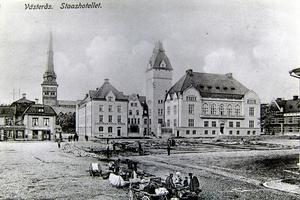 Vykort från 1907.  Stora torget med det nybyggda Stadshotellet. En del tyckte då att byggnaden var ful och alldeles för stor. I dag betraktas Stadshotellet som ett vackert och utmärkt svenskt exempel på byggnadsstilen jugend. De märkliga groparna som syns på bilden är grunderna efter det kvarter som revs för hotellbygget. Stora torget blev dubbelt så stort.