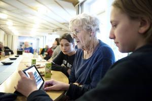 Jesper Lehman och Isak Arvidsson visar Gurli Olsson bilder på Ipaden.