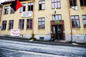 """Hannes Nygård från Lyckliga Gatan sitter på trappan till ockuperade Hotell Aston, för att informera nyfikna förbipasserande om ockupationen. """"Jag är positivt överraskad av den goda respons som vi fått från folk som gått förbi"""", säger han."""