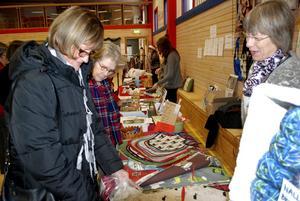 Brokigt julbord. Anneli Eriksson och Gunvi Lyktberg tittar på vad Christina Lindström har att erbjuda på sitt bord vid julmarknaden i Rockhammar. Bild: Klas Holmqvist
