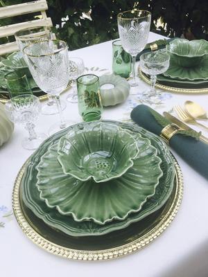 Micael Bindefeld tycker om att bygga på höjden, med många lager av tallrikar och höga vaser på bordet. Handgjort grönt porslin från Helena Bonnier och duk köpt i Addis Abeba i Etiopien.