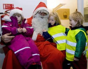 TOMTEMYS. Gästriketomten fick famnen full av barn: Elsa Pettersson, 4 år, och syskonen Ellen och Lina Ivarsson, 6 och 5 år gamla.