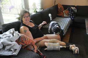 Ingela Sjöberg i soffan ihop med tiken Simba. För Ingela är det viktigt att då och då ta av protesen eftersom det blir varmt och hon får blåsor.
