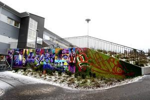 Rolfcarlwerner var här. Livet i Sätra som målning på betongvägg. Den syns tydligt både från bilvägen och cykelbanan.
