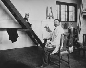 Carl Larsson i sin ateljé i Sundborn. Sannolikt var det här Tunaflickan Emma Hellström fick sitta modell och låna sina vackra drag till såväl Fredrika Bremer som målningen av Den Heliga Birgitta.