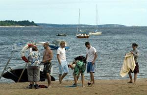 Ingrid Lagerlöf från Miljökontoret sätter upp varningslappar på stranden.