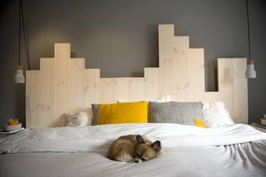 Paret har en minst sagt originell sänggavel. Golvplankorna fick följa med en bit upp på väggen.