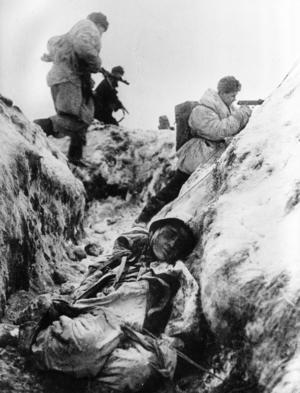 I början av december gick Röda armén till motanfall och pressade tillbaka tyskarna som då stod strax utanför Moskva. På bilden sovjetiska soldater i vinteruniform. En död tysk soldat ligger i skyttegraven.   Foto: APN/TT