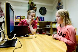 Klara Bolin i klass 2 läser en liten berättelse på skärmen för Ida Bergman. 250 barn ska i dagarna genomgå testet.