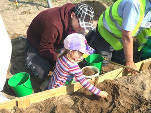 I en sandlåda fick barn pröva på att göra utgrävningar. Här fyraåriga Varja Engman-Relefors med pappa John Relefors.
