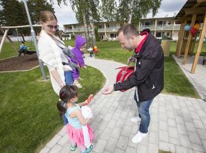 Maiia Deeb, 3 år, får en glass av Fredrik Olsson som jobbar på Hags Parklek, vilka har levererat gungor och klätterställningar. Maiia kom i sällskap av lillebror William Deeb och mamma Maria Puzankova.