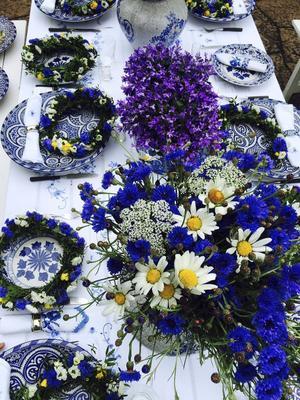 Midsommardukning där blomsterkransar har lagts på tallrikar från Hanoi och Marrakech.