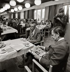 """Palme i Smedgården. Här besöker Olof Palme Smedgården och studerar Nerikes Allehandas Norasida med rubriken """"Olof Palme till Nora -Talar vid Rådhuset"""". Vid bordet i sitter Helge Harsbo som var kommunaldirektör i Nora år 1975. Ur Åke Mossbergs bildarkiv."""