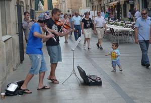 Härlig musik från ett par gatumusikanter och den liie pojken dansar av både glädje och förundran.