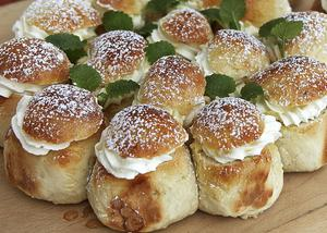 Små semlor bakade tillsammans i form, fyllda med hackad mandel och citronmeliss.