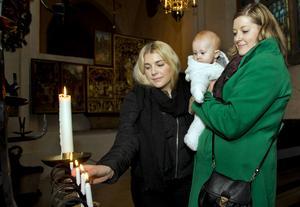 Ljus stund. Lovisa och Camilla Linder tänder ett ljus i Domkyrkan till minne av sin mamma Carina Linder som gick bort i cancer i somras. Hon fick  träffa sitt barnbarn Signe, nu sex månader, något som hon sett fram emot.  Nu är döttrarna med i en kampanj för att samla in pengar till cancerforskning. Foto: Rune Jensen