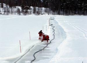 Här sågar Mats Garmager upp en isränna mellan Anviken och Värviken i Revsundssjön. Sträckan är 800 meter och Mats måste såga två gånger för att kabeln ska kunna läggas ner.