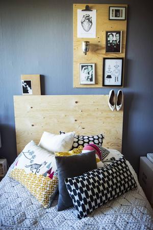 En sänggavel i trä matchas med en tavla på väggen där gamla bilder hänger.