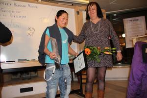 Majs Keller tar emot priset i form av diplom och blommor från Maria Hansson Nielsen.